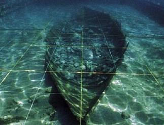 """El segundo de los barcos fenicios, el conocido como """"Mazarrón II"""", está casi completo y conservado in situ frente a la playa de La Isla. De unas dimensiones de 8,10 m. de eslora y 2,25 m. de manga, contaba con la totalidad del cargamento, constituido fundamentalmente por lingotes de mineral de plomo. También se localizó el ancla, de tipo denominado de """"caña, cepo y uña"""", siendo el ejemplar más antiguo conocido hasta la fecha en el Mediterráneo (Foto del Museo Nacional de Arqueología)"""